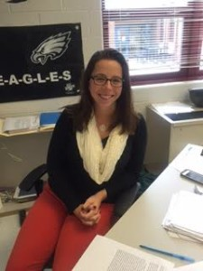 AP economics teacher Kieran Sweeny sits at her desk welcoming students into her classroom.