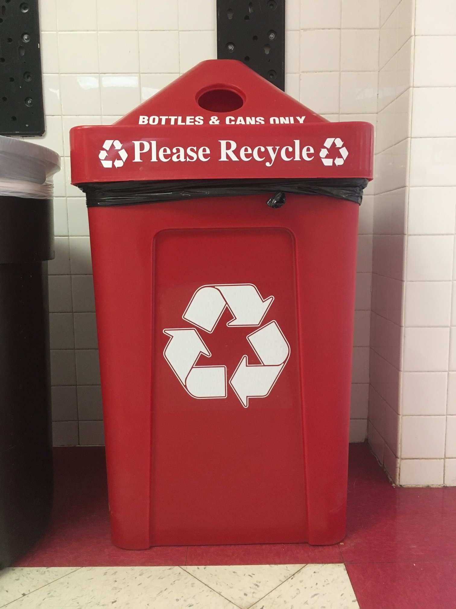 One of the new red recycling bins located next to the rock entrance