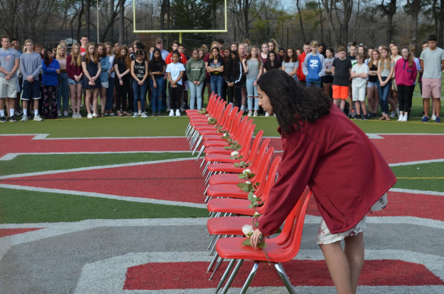 Senior Yasmin Berrada places the last rose, culminating the vigil. Each victim of the shooting had a minute of silence dedicated to their memory. (photo by Maren Kranking)