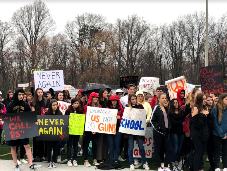 Students+carry+signs+against+gun+violence+at+the+student-led+walkout+on+March+1.+During+Highlander+Time+8%2C+students+gathered+on+the+football+field+to+speak+out.