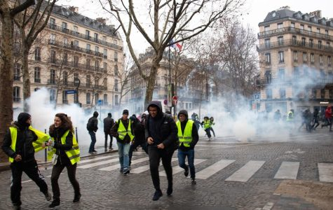 The gilet jaunes (Yellow Vests) run the streets of France in the midst of the fire smoke. The yellow vest is a symbol of civilian resistance to the raise of fuel taxes and other issues deemed problematic. (Photo obtained via Wikipedia.com under a Creative Commons license)