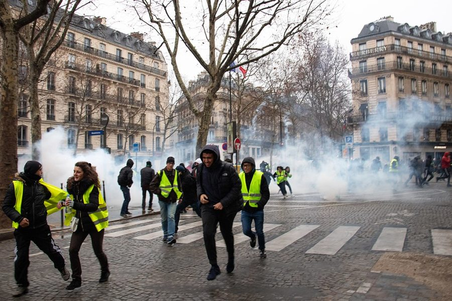 The+gilet+jaunes+%28Yellow+Vests%29+run+the+streets+of+France+in+the+midst+of+the+fire+smoke.+The+yellow+vest+is+a+symbol+of+civilian+resistance+to+the+raise+of+fuel+taxes+and+other+issues+deemed+problematic.+%28Photo+obtained+via+Wikipedia.com+under+a+Creative+Commons+license%29