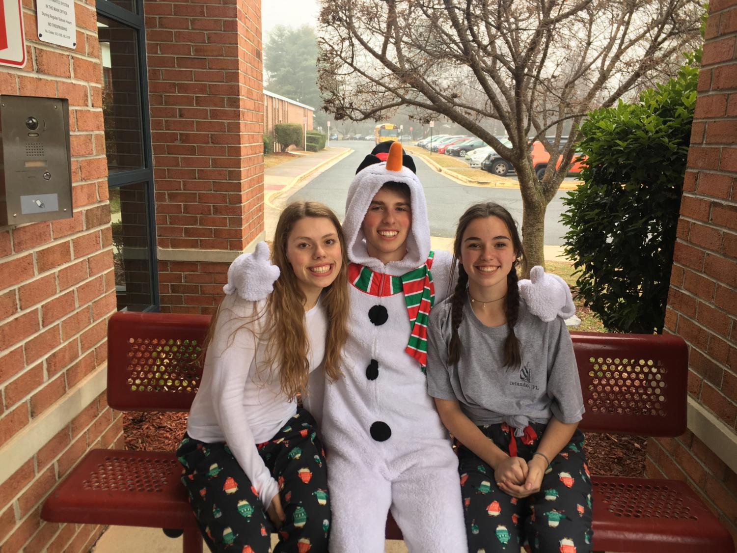 Sophomore Skye Sunderhauf (left), junior Zach Anderson (middle), and sophomore Katie Romhilt (right) show off their school spirit. They dressed up for comfy clothes day two days before the start of winter break. (Photo by Emily Jackson)
