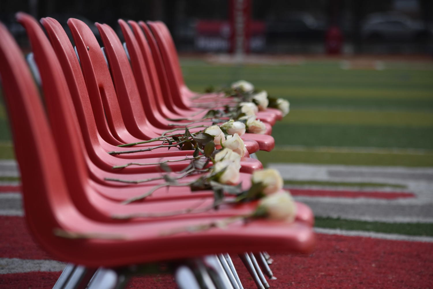 17 chairs are set on the middle of the football field to honor the lives of those lost during the Parkland shooting