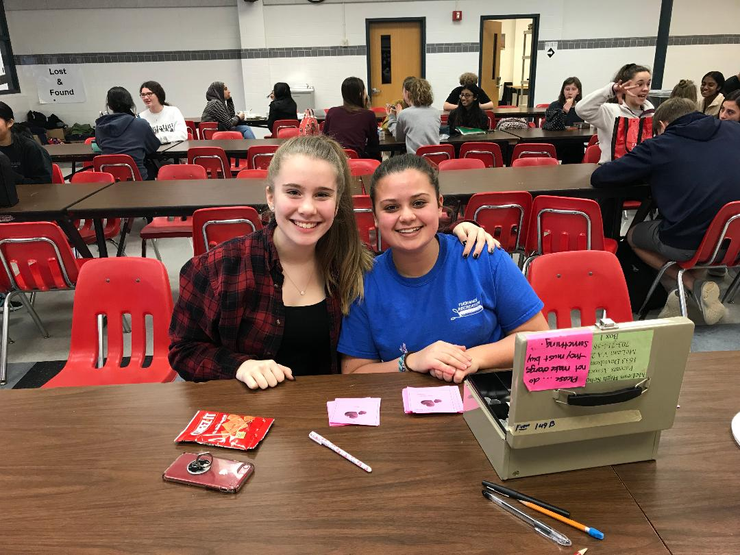 Armonia Choir member, sophomore Francesca Bellora (left), and Armonia and Madrigals Choir member, sophomore Elizabeth Hughes (right), sit in the cafeteria as they manage the Singing Valentines sales. Singing Valentines are for sale for $5 a song. (Photo by Zach Anderson)