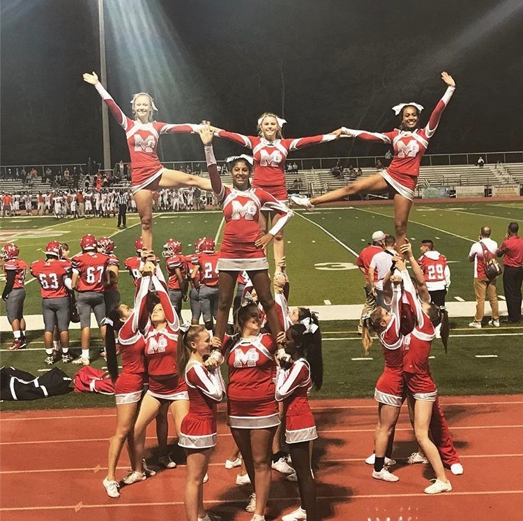 CHEER+PYRAMID%E2%80%94Centered+in+the+stunt%2C+Malhotra+cheers+with+her+team+at+a+Friday+night+game+in+the+2017+season.+The+cheer+team+performs+stunts+and+cheers+throughout+every+football+game.+%28Photo+courtesy+of+Anika+Malhotra%29