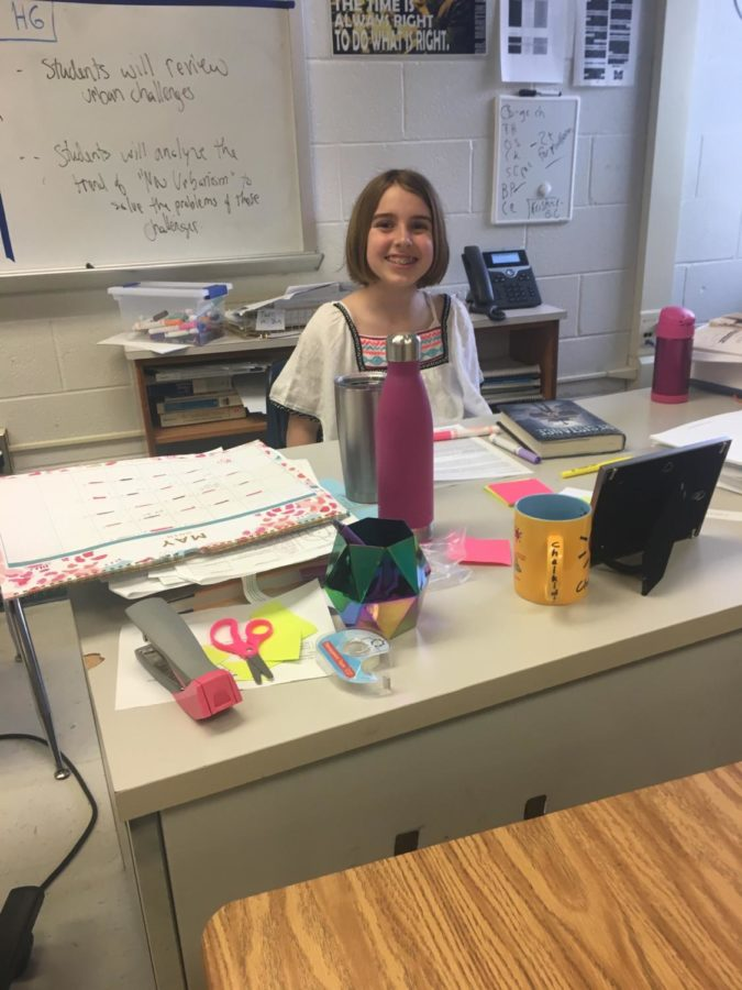 Emer Johnson's daughter Nora smiles from behind her mother's desk. Nora offered to help her mother pass out papers and was able to answer questions about her mother's teachings. (Photo by Emily Jackson)