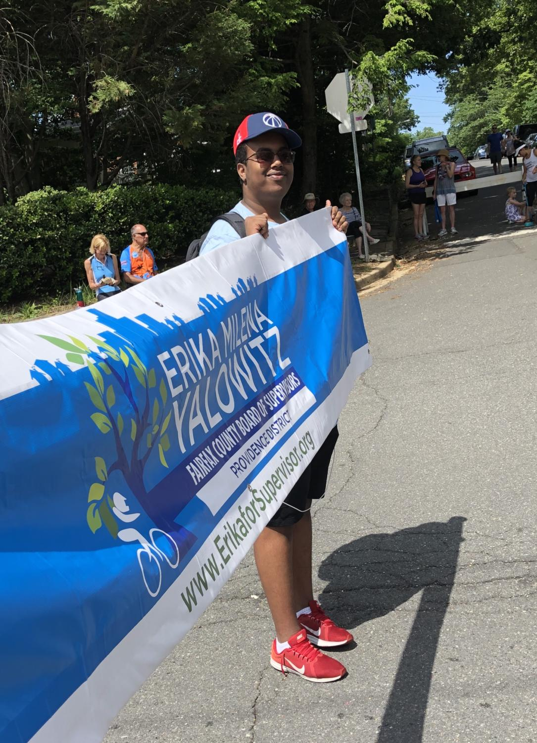Sophomore Mohamed Mohamed showed his support for Erika Yalowitz by holding her banner during the Memorial Day parade in  Falls Church on May 27.