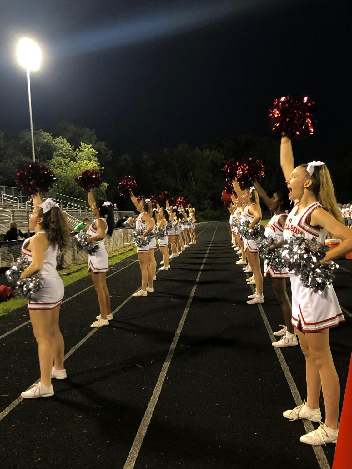 The+varsity+cheer+team+turn+toward+the+stands+and+start+a+cheer.+The+cheerleaders+travel+with+the+football+team+to+every+game.