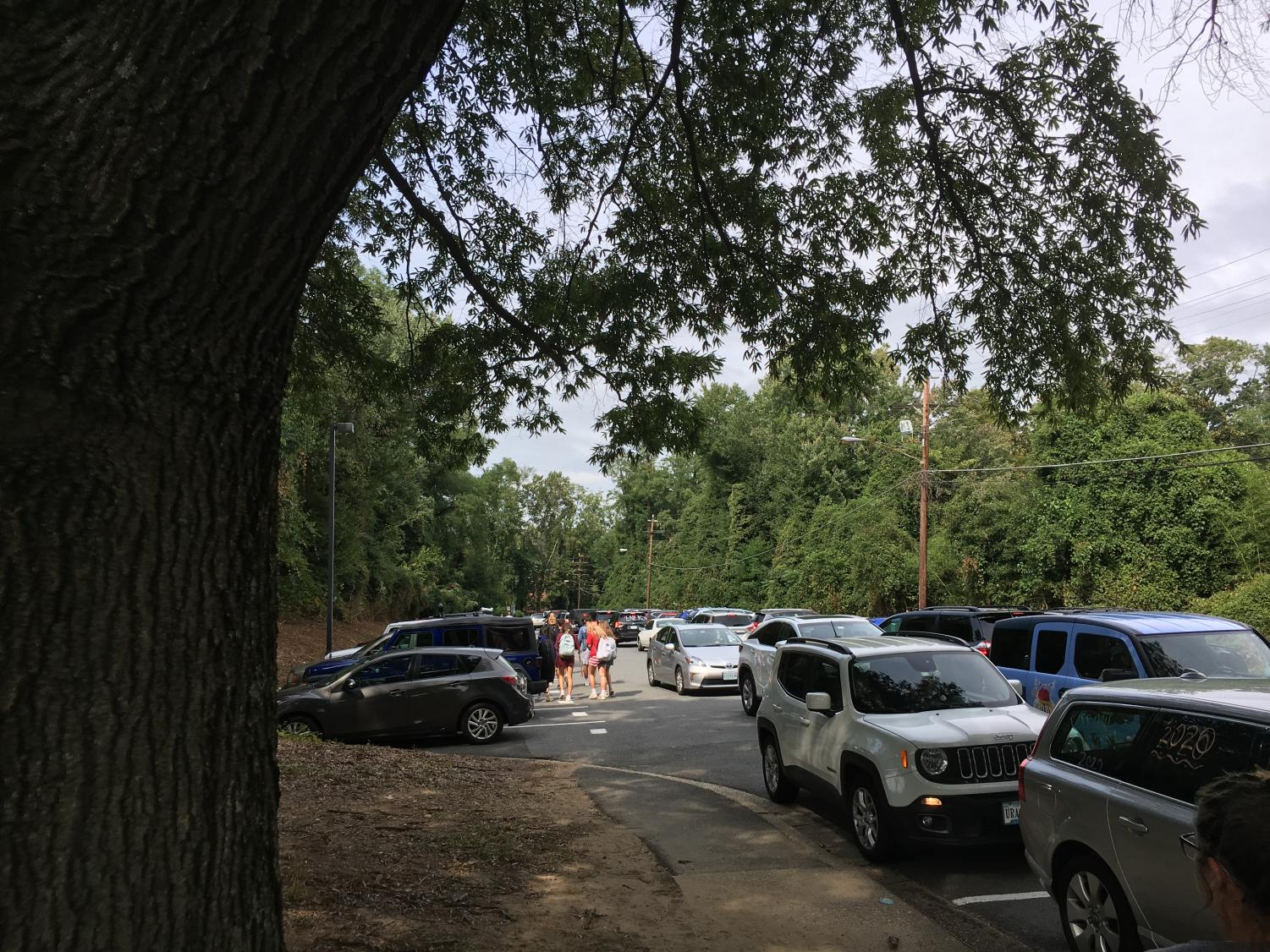 Rush Hour--Students try to drive home in the gridlock that has infiltrated this two-way street. Cars in the new parking spaces are blocked by the long line of vehicles behind them.