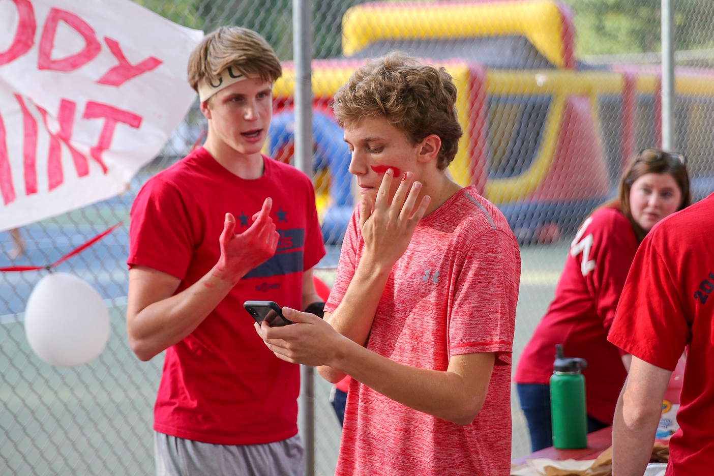 Sophomore Aaron Bremser and senior Pierce Laszlo work to get properly spirited for the tailgate. Since the game is a red out, they deck themselves up in red paint to support the Highlanders.