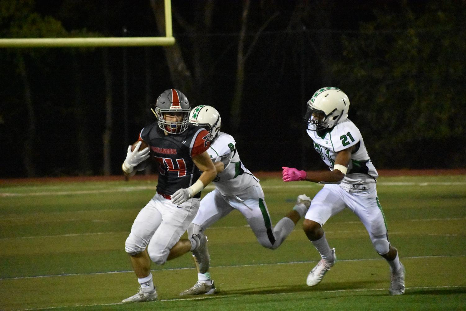 Full Speed Ahead- Running back Ryan Jessar races down the field past two Wakefield defenders. He led the Highlanders offense in the exciting Homecoming win.
