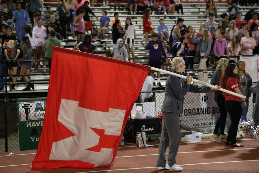 Cheerleader+Atticus+Gore+holds+the+flag+with+a+big+M%2C+cheering+up+McFootball+and+the+crowd.+The+usual+football+game+brings+students+together+to+enjoy+their+Friday+night.+