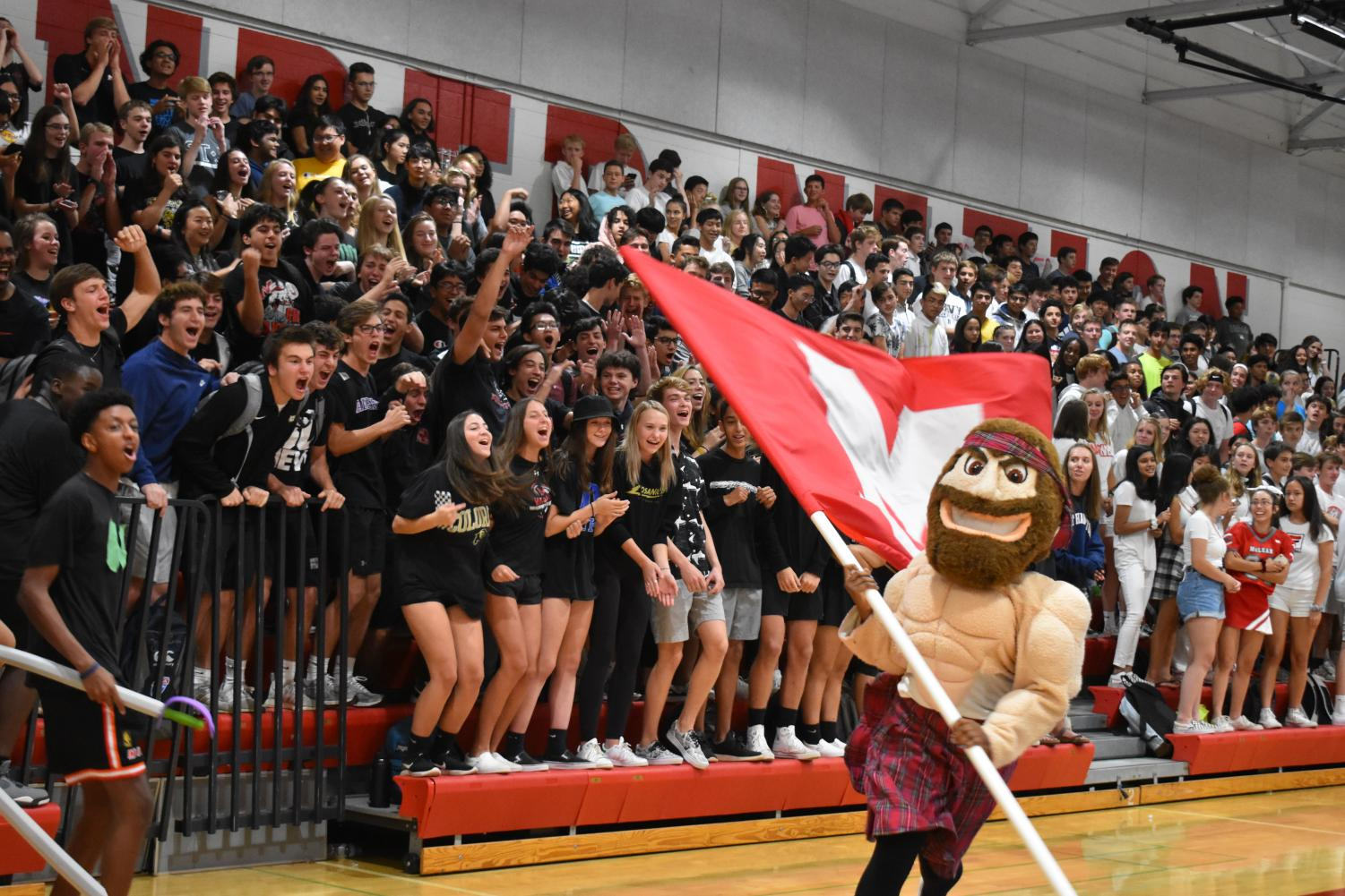 SECTION SCREAMS- Angus runs around the gym with our flag as the grades compete to be the loudest