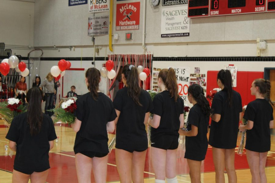 The underclassmen on the McLean volleyball team hold gifts for the seniors as they walk out. The Highlanders went against Washington-Lee for Senior Night.