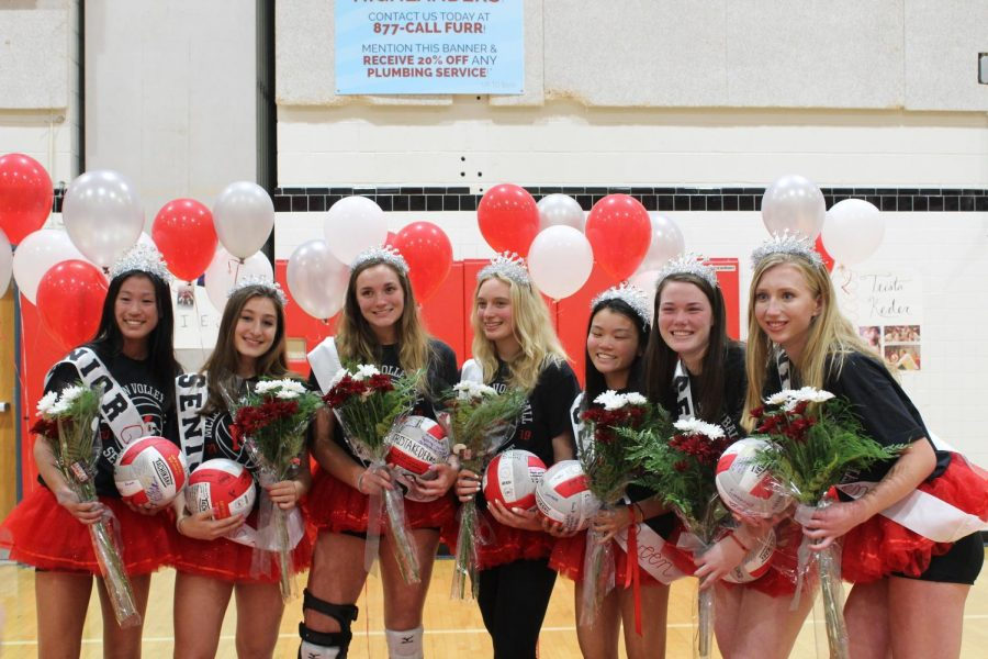 The seniors on the McLean volleyball team pose for a picture together. The gym was decorated especially for senior night.