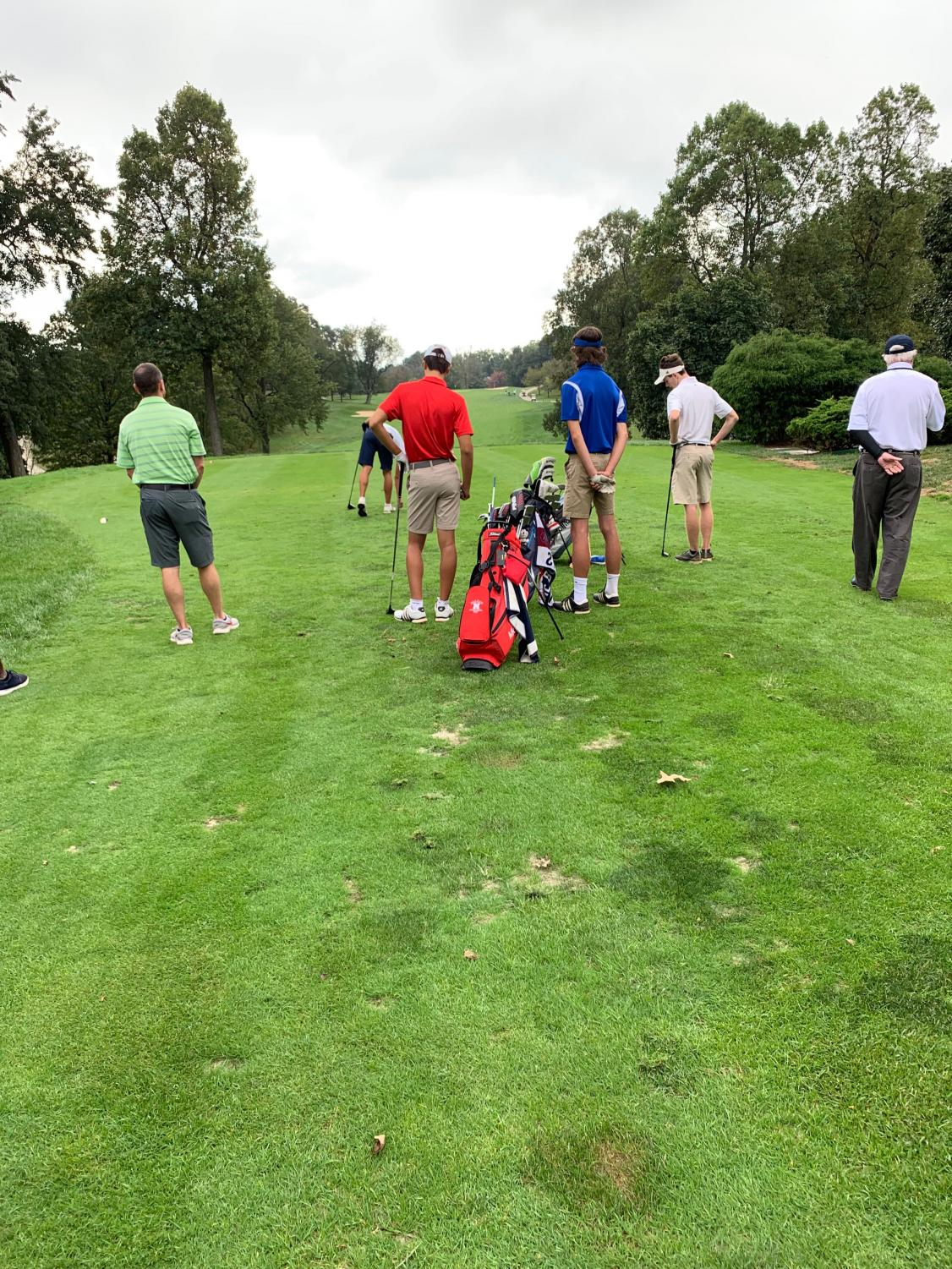 The Varsity Golf team tees off in the Liberty District Golf tournament.