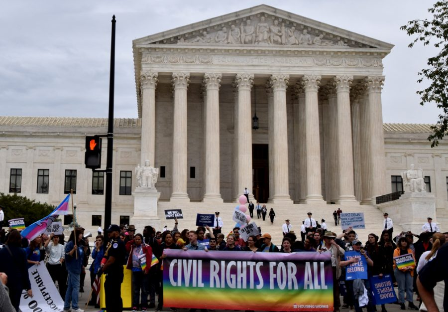 People protest in front of Supreme Court on Tuesday. The court is taking up a major case on whether or not employers can discriminate based on sexual orientation or gender identity.