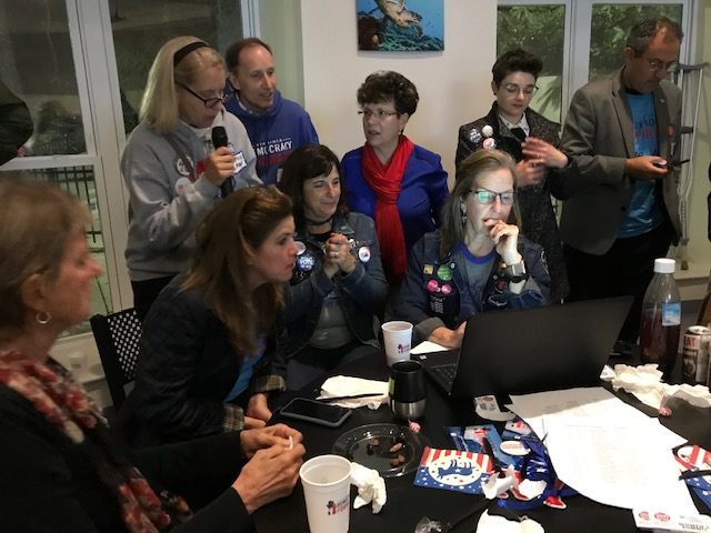 Members of the grassroots group, Virginia Democracy Forward, huddle around a computer on Nov. 5 to watch the 2019 Virginia election results. The Democrats ended up winning the majority in the VA house and senate.