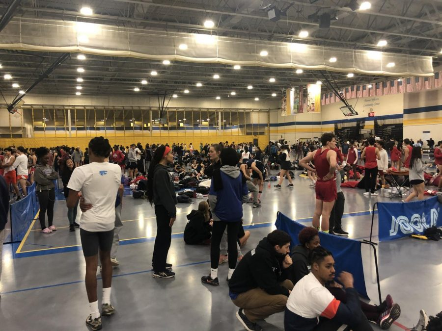 CALM BEFORE THE STORM - Athletes warm up before they compete on Friday night. Some athletes have already ran their events and are supporting their teammates.
