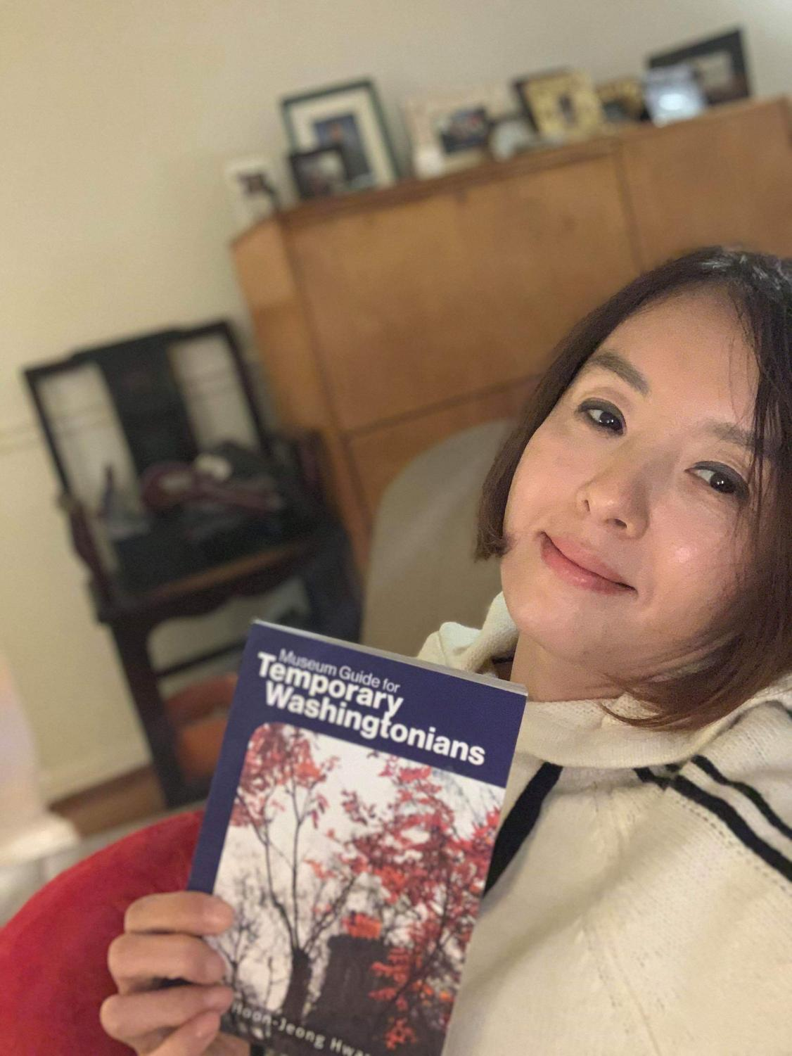 Mrs. Chung poses with her book, Museum Guide for Temporary Washingtonians.