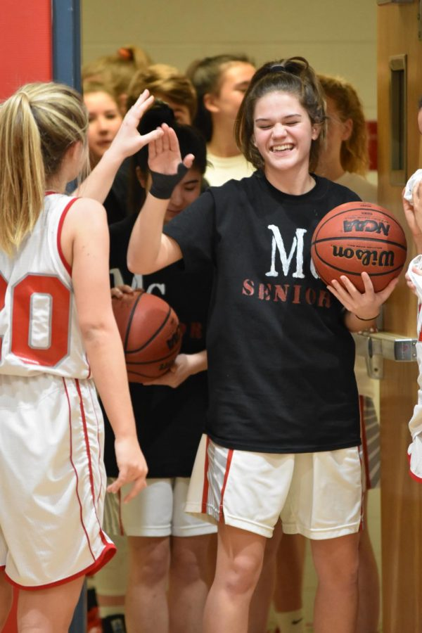 Senior Elly Glenn high fives her teammates as she makes her way into senior night