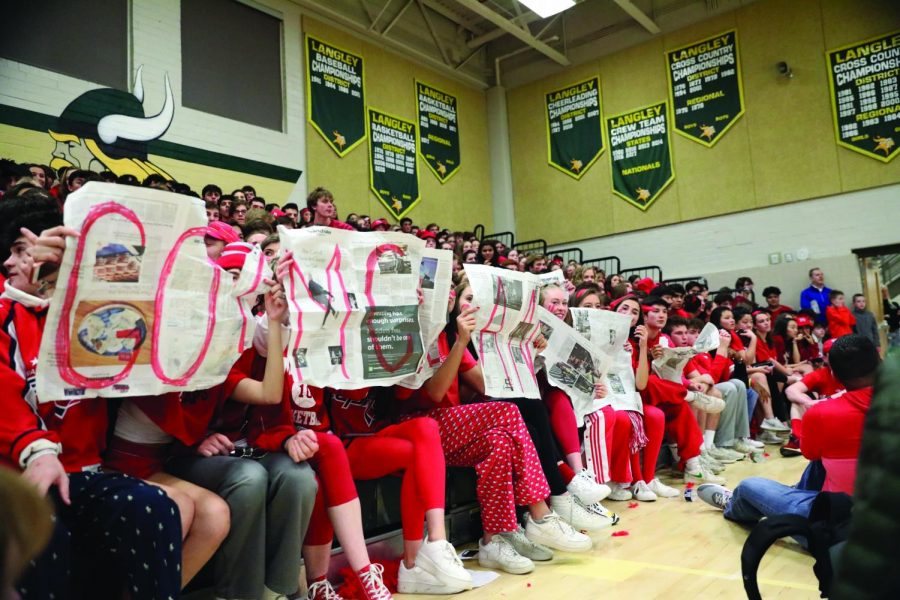 McLean students hold up Go McLean written on newpapers.  The stakes of the match were high as it was played against school rival Langley High.