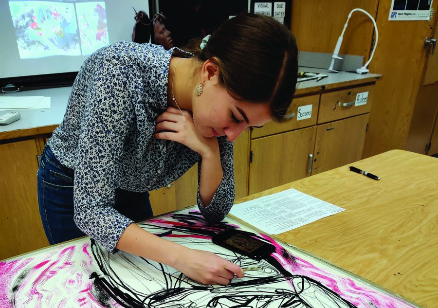 Grace Frazee works on her most recent art piece during class. She is using an exacto knife to cut out lines where she will later place red string.