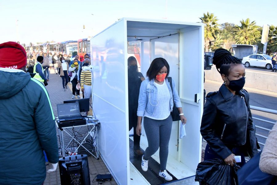 Members of a community are inspected for COVID symptoms before they board the bus. These invasive procedures and social distancing have a negative effect on the mental health of the general population. (Image obtained via  GovernmentZA under a Creative Commons license)