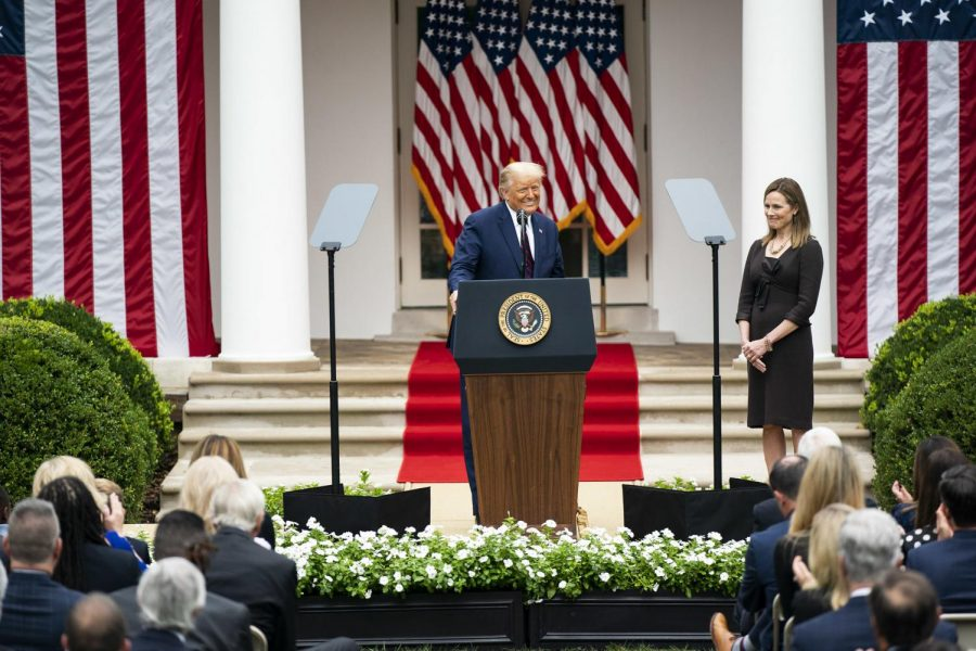 Barrett stands by as Trump introduces her as his nominee for Supreme Court Justice in a Rose Garden White House ceremony. It is still unconfirmed whether this selection will stand with the upcoming election. (Image obtained via The White House on Flickr under a Creative Commons license.)