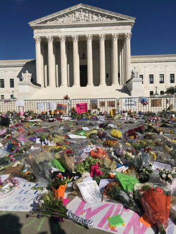 People place flowers and cards in front of the Supreme Court to show their support for the late Justice Ruth Bader Ginsburg