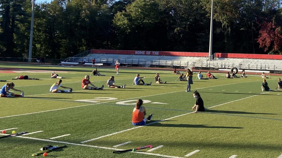 Field hockey athletes stretch during the Oct. 8 green day. The players remained socially distant in order to have a safe practice for everyone who attended.