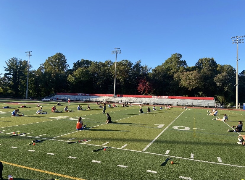 McLean girls field hockey team finishes their practice by stretching. They are spread out across the field in order to maintain social distancing. Photo courtesy of Coach Mary Elizabeth McManus.