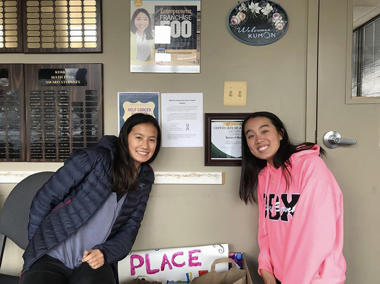Posing For Donos - Founder Olivia Zhang (right) and club officer Thais Rolly display their Kumon donation event gatherings. These donations consisting of toys, books, and games were shipped to the Cincinnati Children Hospital. (Photo courtesy of Xiaowei Zheng)