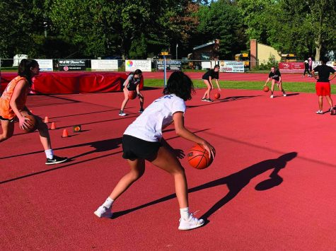 SHADOW ONE-ON-ONE — The girls basketball team begins their Sept. 22 yellow day practice by doing ball handling. Most players have their own balls due to the rule that only two people can touch one ball during the whole practice.
