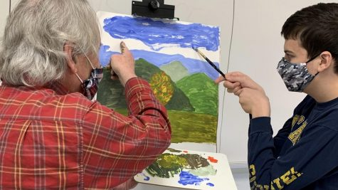 CREATING BEAUTY - Teacher John DeMers works with junior Alex Pisocky on a painting during Highlander Time. DeMers often teaches students techniques that he has learned from his art instructors.