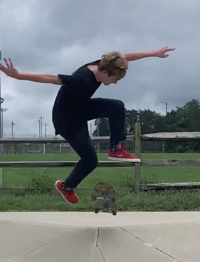 Sophomore Alex Kalhor hits a tre-flip on the sidewalk. Kalhor, Birchfield and Harake take turns recording each other preforming tricks.