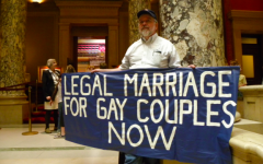 LEGAL BATTLE — A protestor stands outside the Minnesota Senate chamber, urging for the legalization of gay marriage. Gay marriage is major example of when legislators have taken an excessively long time to grant basic rights because of different political ideologies.