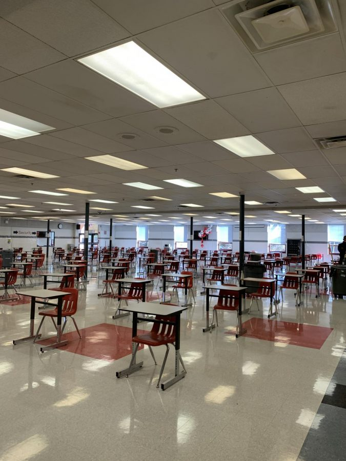 The cafeteria set-up displays spread out desks, all facing one way. All of these desks have QR codes for students to scan for contact tracing.