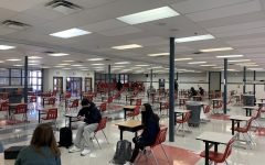 Students eat lunch in the cafeteria. Desks are spaced six feet apart to ensure social distancing.