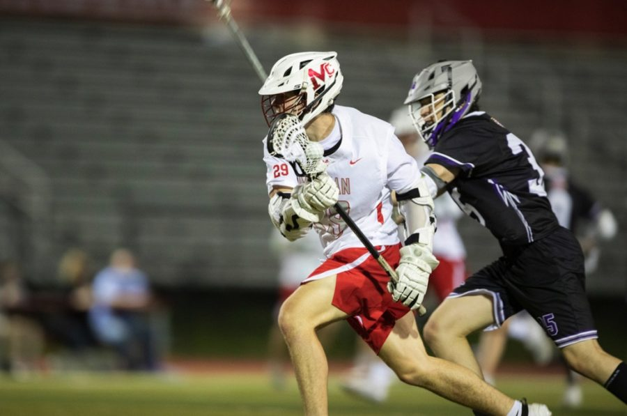 La-Crossing The Field - Senior attacker Alec Butler (#29) cradles the ball past a Chantilly defender on Apr. 29. Butler and the rest of McLean's offense scored 7 goals in this regional matchup.