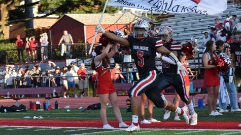 Highlander Team captain Calvin Thinley sprints onto the field, waving the school flag.