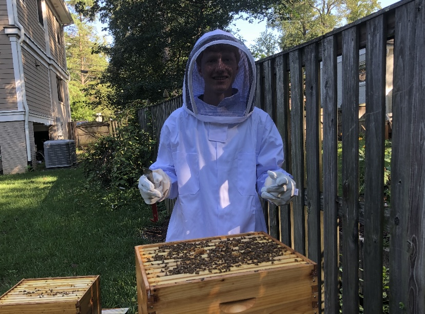 Jordan Coopersmith cares for his bees. He wears a suit to protect himself, as well as smoke to calm the bees.