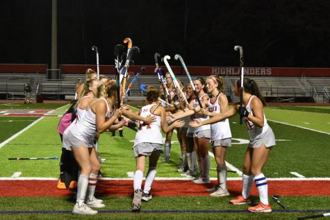 Senior Audrey Loucks runs through the tunnel made by her teammates. Each starting player was announced and ran through a tunnel formed by their teammates and hockey sticks.